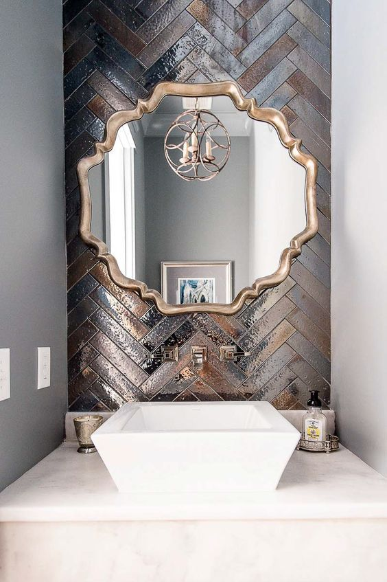 a gorgeous statement wall done with metallic tiles of different shades and clad in a herringbone pattern