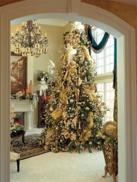 a large Christmas tree with lots of vintage ornaments in gold looks amazing