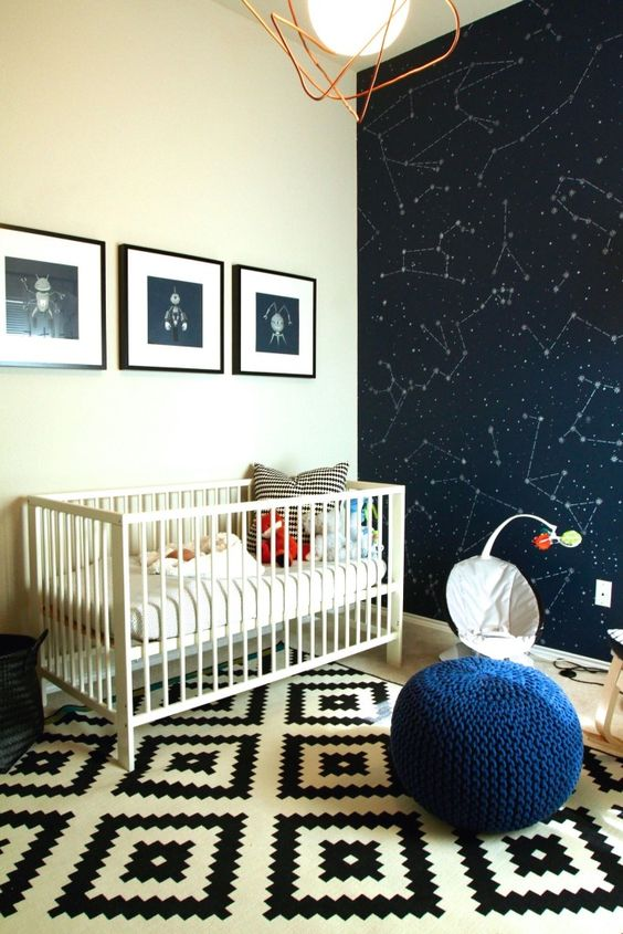 a space themed nursery with a constellation statement wall, fun artworks and a navy pouf