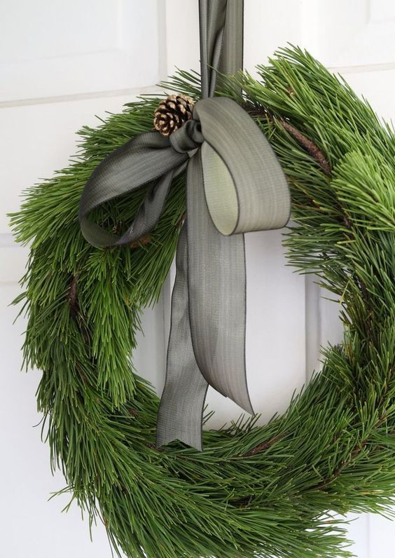 an elegant evergreen wreath with a pinecone and a grey ribbon bow