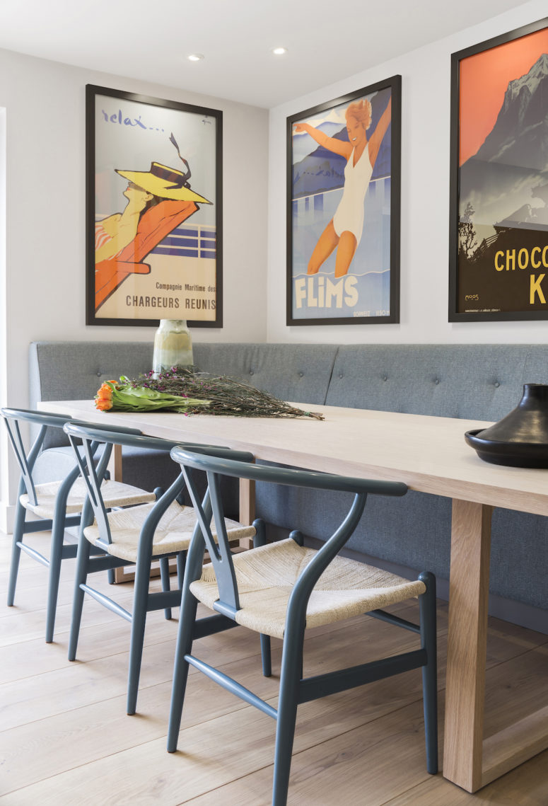 Colorful vintage posters that belong to the owners were used throughout the house including this dining zone