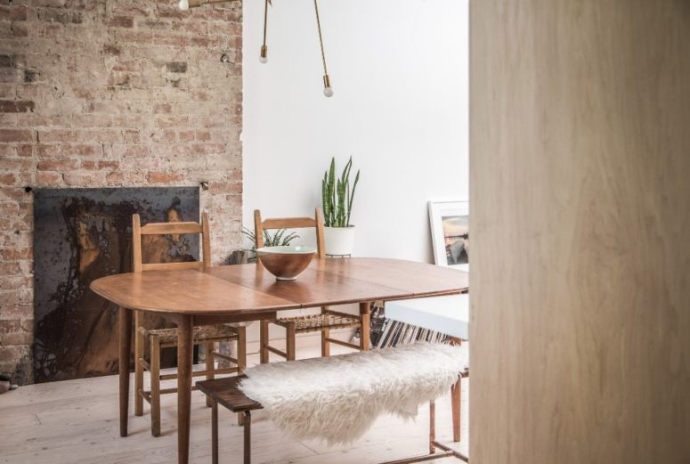 The dining space is done with a mid-century modern dining set, a burst lamp and a brick wall with a built-in fireplace