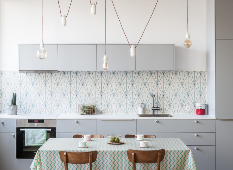 The geometric kitchen backsplash stands out nextot the grey kitchen cabinets, and lamps hanging on red cord add an industrial feel