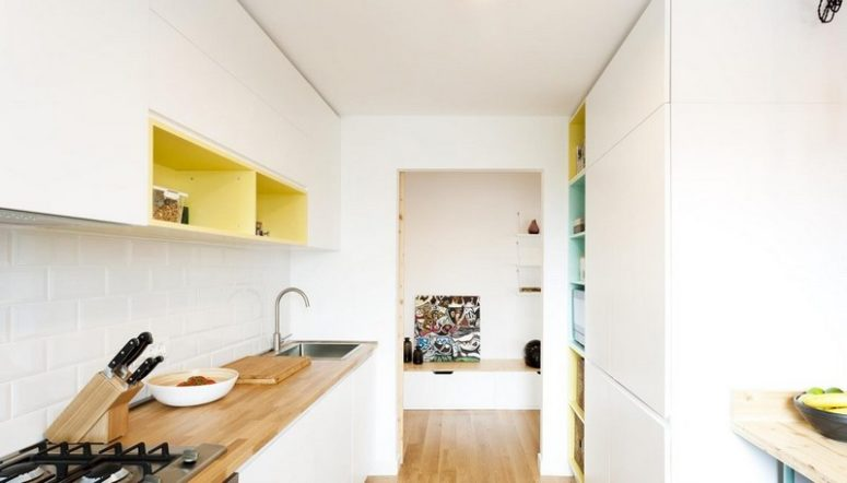 The kitchen is minimalist, with sleek white cabinets, colorful inside of cabinets, butcher's block tops