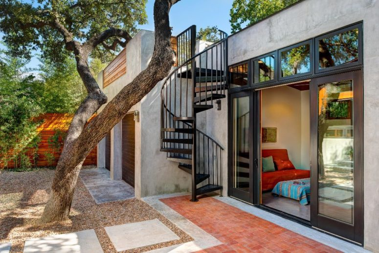 The patio is manicured, its hardscaping and greenery along the fence and a tree bring some shade here, the staircase leads to a rooftop terrace