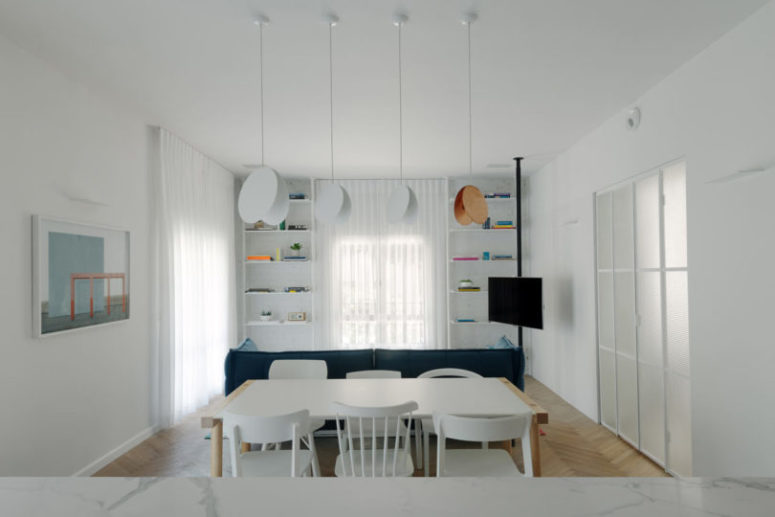 The pendant lamps are very eye-catching and the dining space is located right behind the sofa