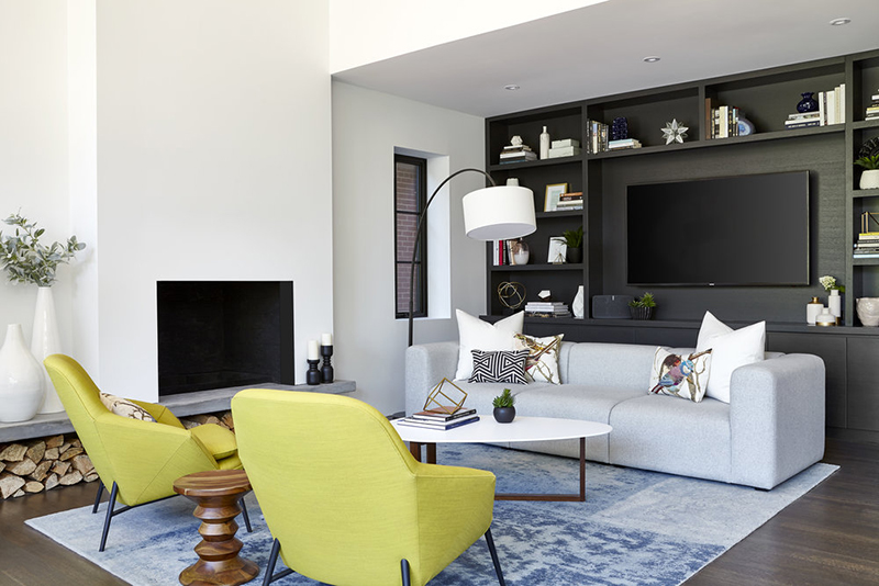 The sitting space united with the dining one is done with neon yellow chairs and a grey TV wall unit