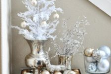 04 a glam Christmas display with gold and silver ornaments, a deer and snowy branches