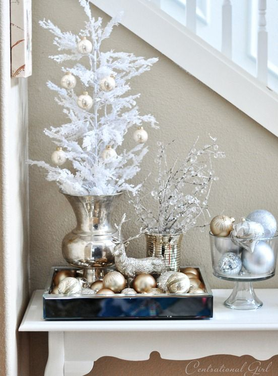a glam Christmas display with gold and silver ornaments, a deer and snowy branches