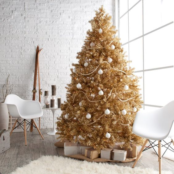 a gold Christmas tree decorated with white ornaments is great for a glam space