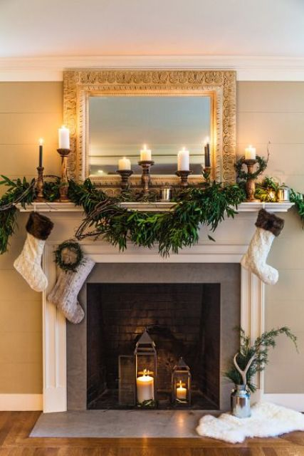 a lush greenery garland, candles and stockings plus candle lanterns inside a non-working fireplace