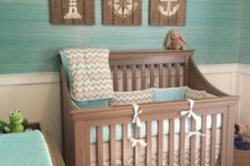 04 ocean-themed nursery with reclaimed wood artworks and a turquoise wall and bedding