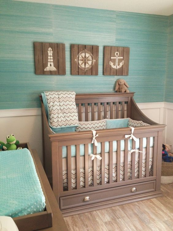 ocean-themed nursery with reclaimed wood artworks and a turquoise wall and bedding