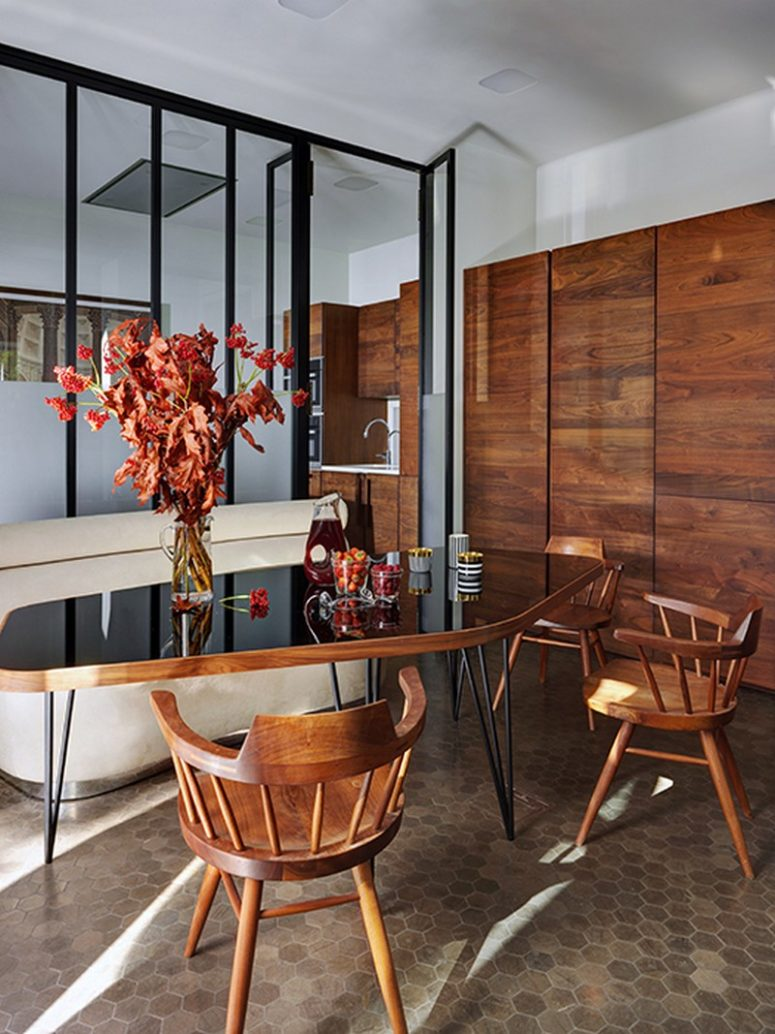 The dining space is done with a rich-colored wood cupboard, chairs and a chic table with a black glass top