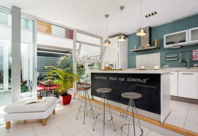 The kitchen features a chalkboard kitchen island and it's located on a platform to separate the space