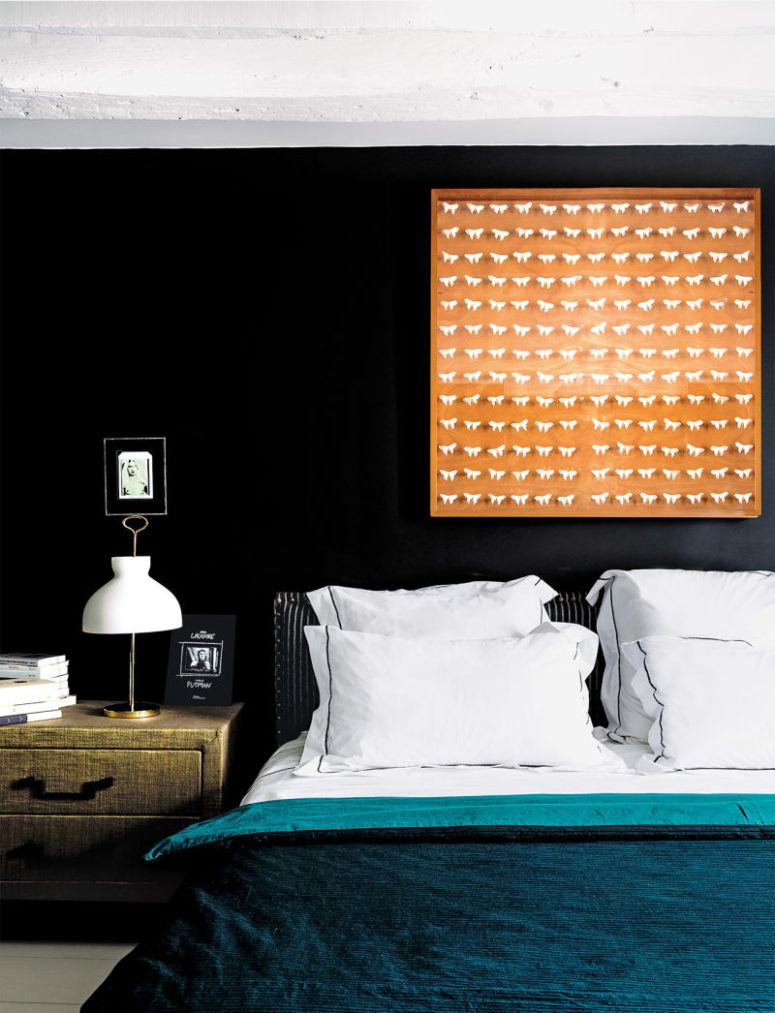 The master bedroom is done with a turquoise bedspread, with an orange artwork and a fabric covered nightstand