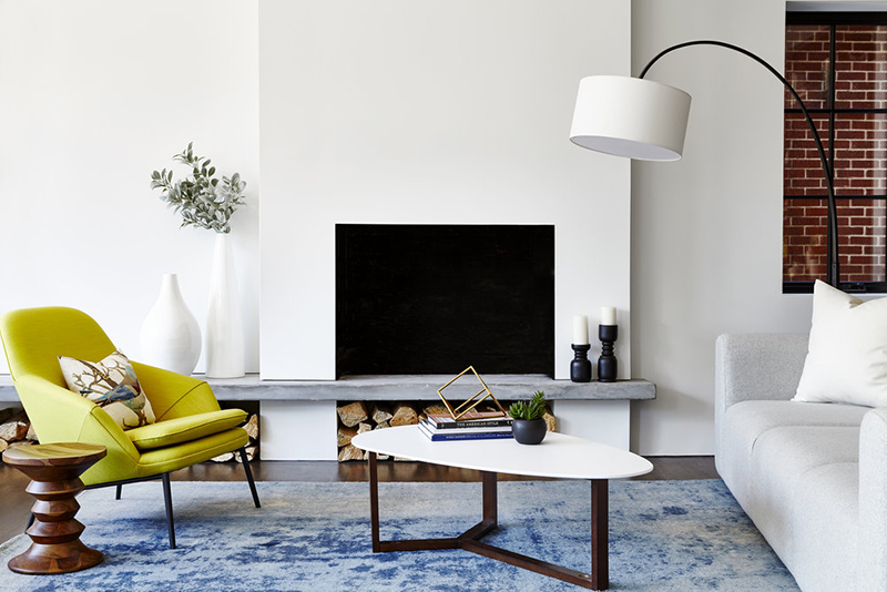 There's a built in fireplace and a worn blue rug