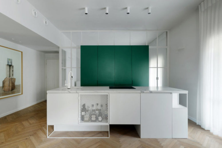 There's a large green cube for storage and a large kitchen island with lots of space for cooking