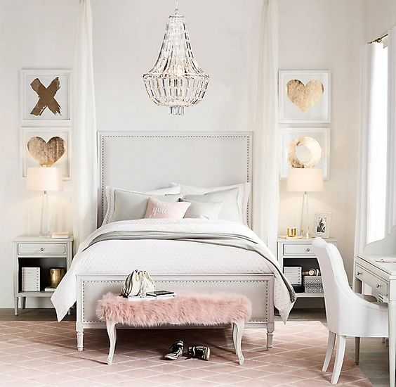a bedroom done in cream and light grey, a pink fur bench and gold touches