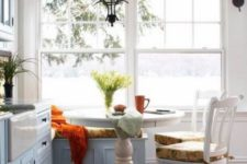 05 a cozy coastal breakfast space with a white pedestal table, some colorful printed chairs and a bench