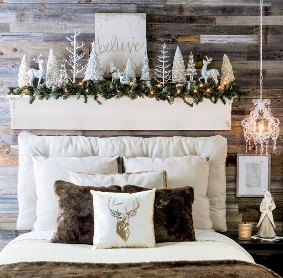 a headboard display with deer, shiny Christmas trees, a fir garland and lights