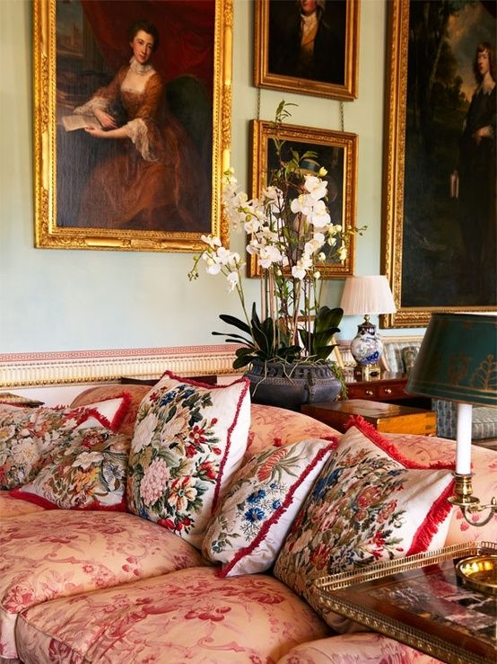 a large upholstered sofa and pillows are with different floral prints