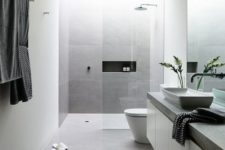 05 a minimal bathroom in white and grey, a glass shower and a stone countertop