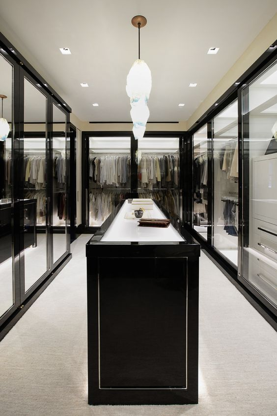 a stunning walk-in closet with framed glass doors and lots of light looks very spectacular