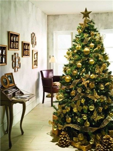 an emerald tree with gold ornaments looks chic and contrasting, this is a glam combo for the holidays