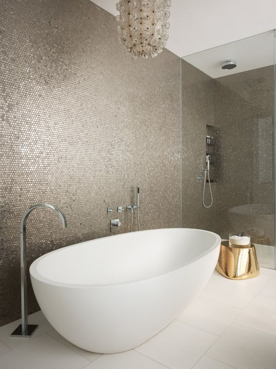 shiny penny tiles, a shiny brass stool and a crystal chandelier are ideal for a glam space