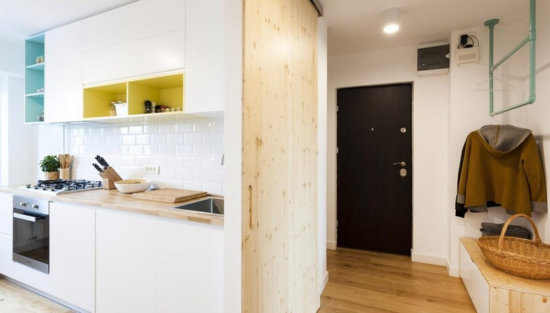 The entryway features some colroful hangers, a storage unit and a wooden wall