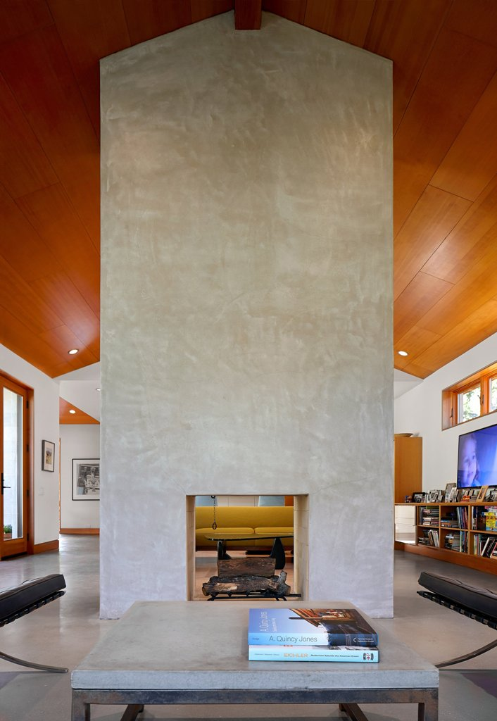The fireplace with a concrete wall up to the roof is seen from all the sides and there's a matching coffee table