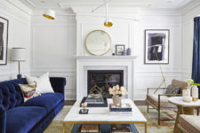 06 The living room is done with a navy sofa and curtains, with a built-in fireplace and mauve chairs, metallic touches make the space chic