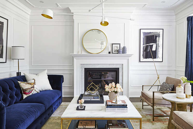The living room is done with a navy sofa and curtains, with a built in fireplace and mauve chairs, metallic touches make the space chic