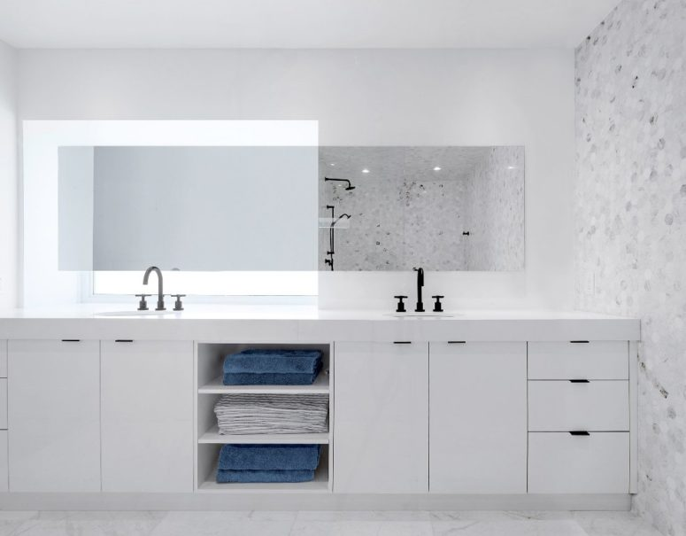 The master bathroom is done in white and marble, there's a large double vanity with much storage