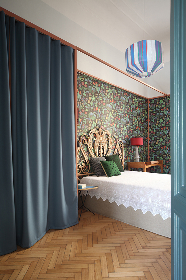 The master bedroom was done with bold flroal wallpaper and a bed with a very eye-catchy headboard