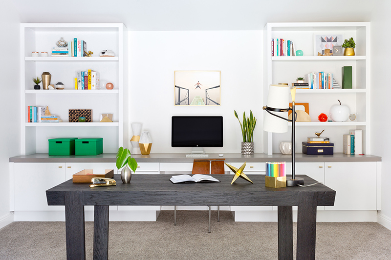 The workspace is light and airy, with built in furniture and lots of colorful accessories