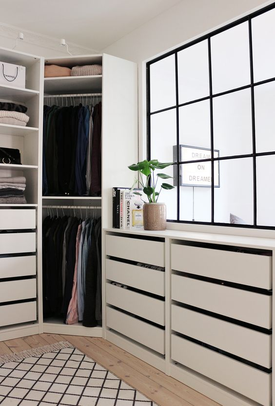 A Comfy Modern Walk In Closet With A Large Window And Cabinets With Drawers