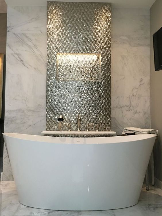 a marble statement wall and a shiny penny tile statement to highlight the bathtub
