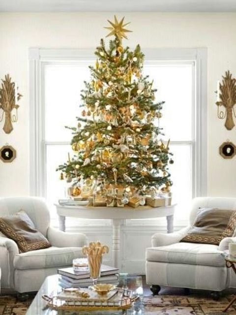 a small tabletop Christmas tree with gold and white ornaments looks contrasting and festive
