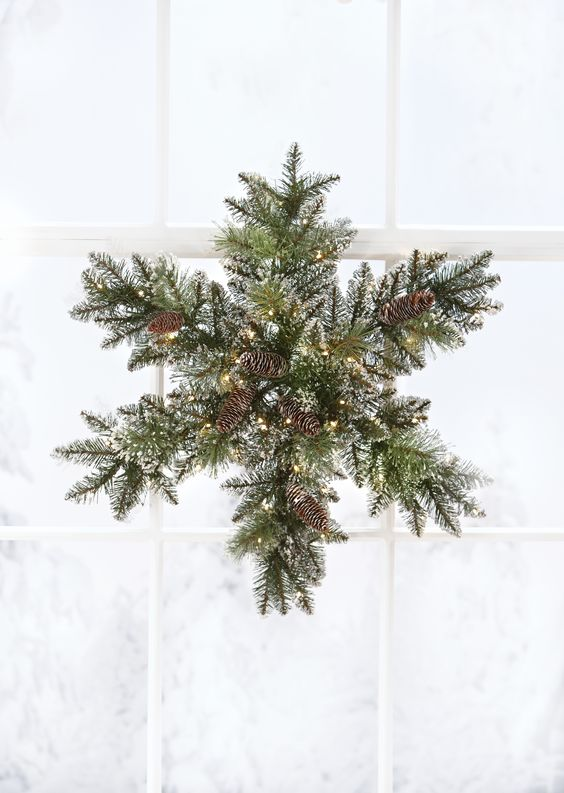 a snowy evergreen Christmas wreath with pinecones and lights shaped as a snowflake