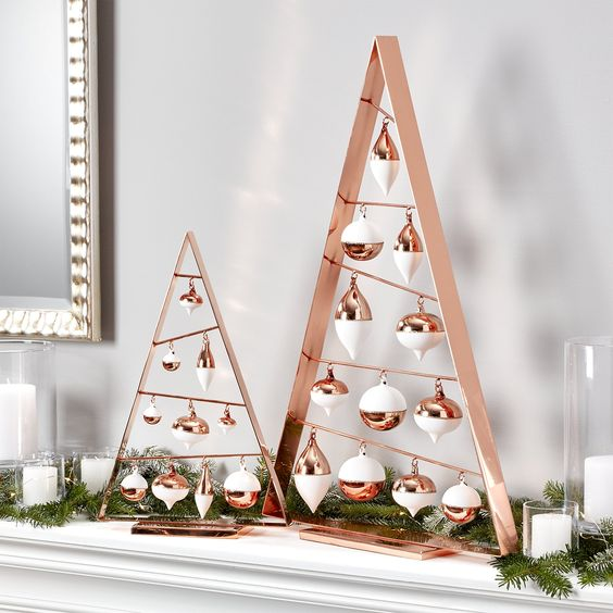 copper frame Christmas trees with white and copper ornaments, a fir garland and candles
