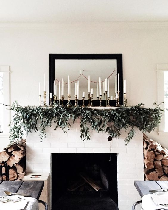 elegant mantel decor with an evergreen garland and lots of candles is easy to recreate and looks cool