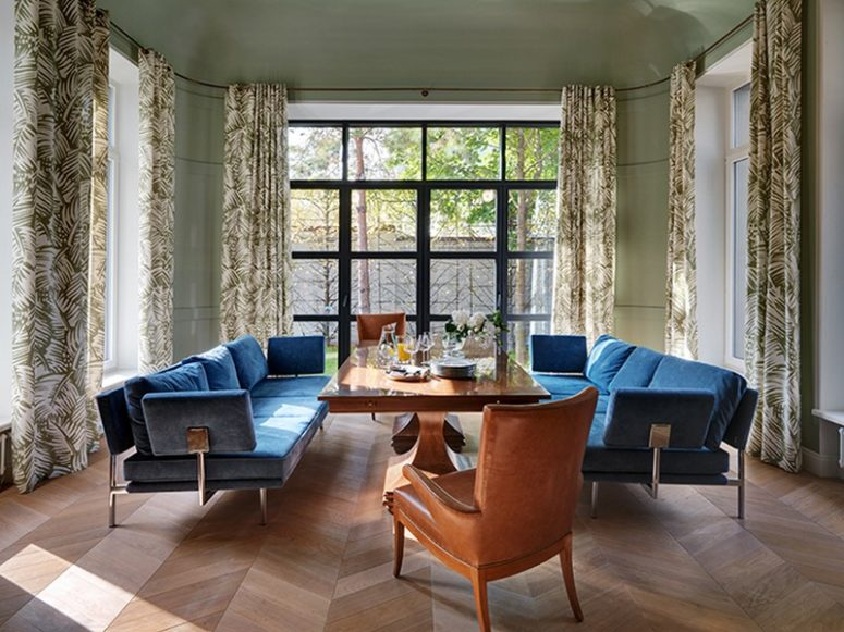 A separate dining room with a large table and two upholstered sofas is filled with light