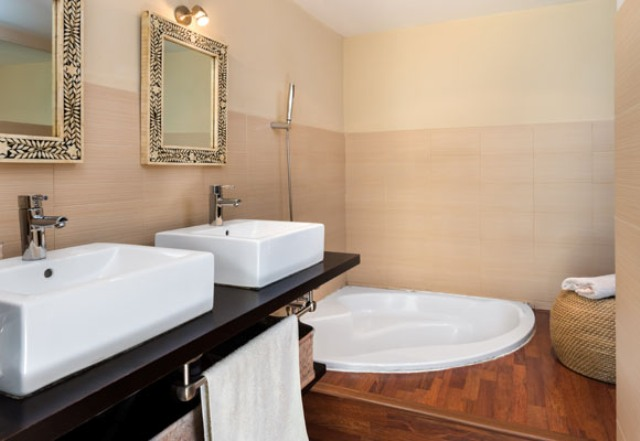 One of the bathroom features a sunken bathtub, a double vanity with sinks and a jute ottoman