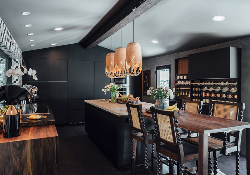 Rich colored wood touches, eye catchy stools and pendant lamps over the kitchen island add eye catchiness to the space
