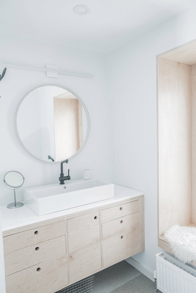 The bathroom is also decorated in white, with light-colored plywood and some simple pieces, it's filled with light