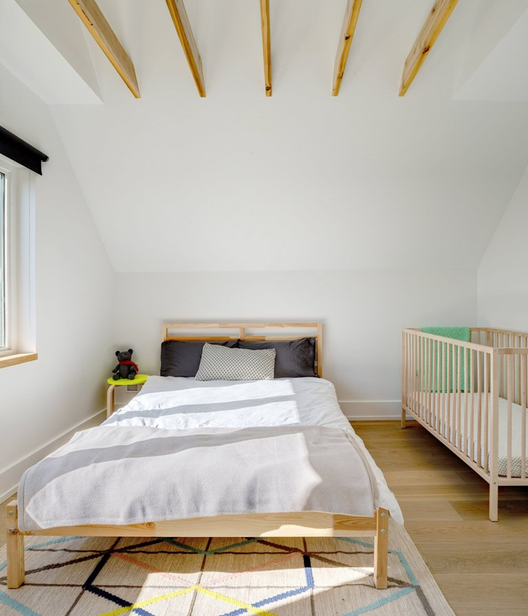 The bedroom features a bed, a colorful geo rug and a baby's crib