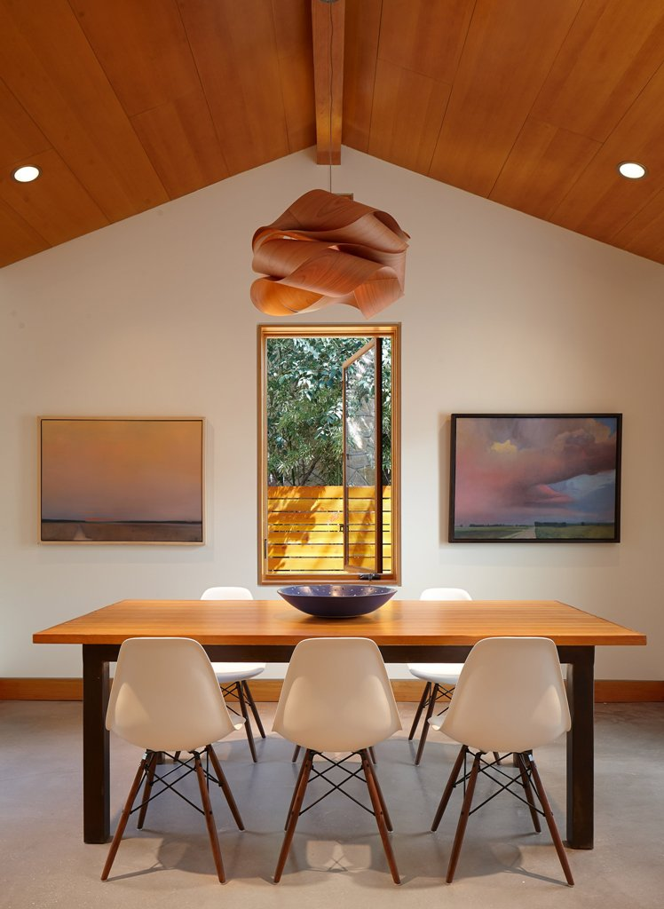 The dining space is marked with artworks, a window and a very eye-catching pendant lamp of curved plywood
