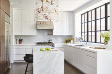 07 The kitchen is done with sleek white cabinets, a wooden wall with built-in appliances and marble countertops